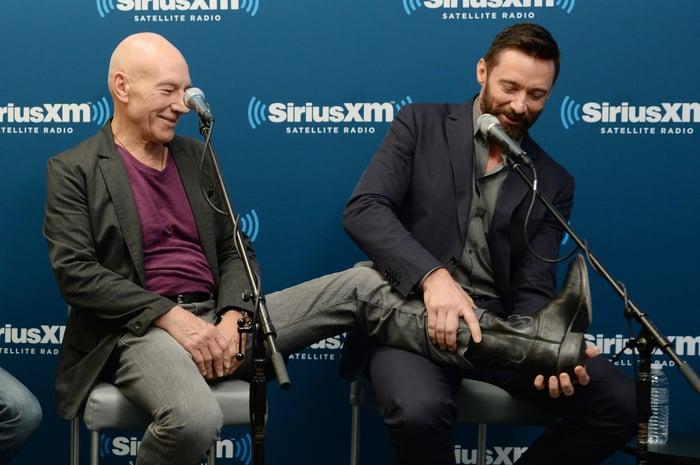 Patrick Stewart putting his leg on Hugh Jackman's lap during a Sirius XM Town Hall interview.