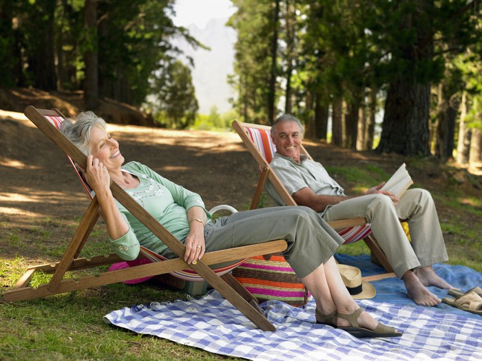 Two retirees relaxing outdoors.