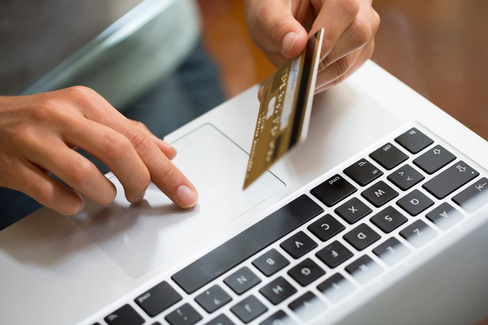 A person holds a credit card over a laptop.