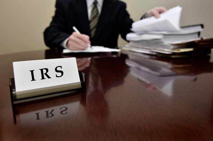 An IRS agent in a suit examining paper filings at his desk.