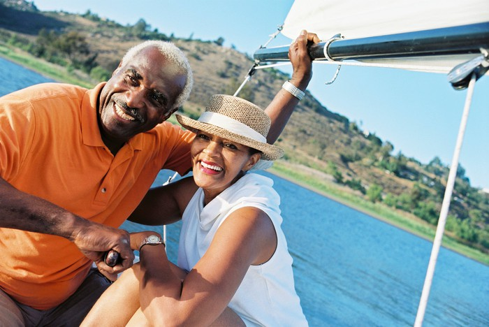 A smiling senior couple enjoying time out on the water on their sailboat.