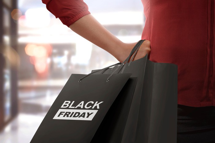 A woman holds a Black Friday shopping bag.
