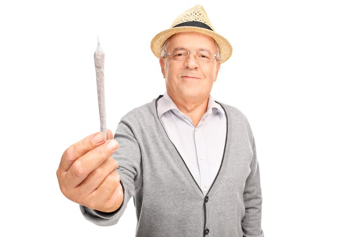 A senior man wearing a straw hat and gray cardigan sweater holding a rolled cannabis joint in his extended right hand.