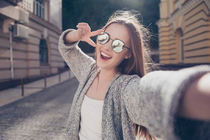 Image of young woman smiling and taking a selfie.