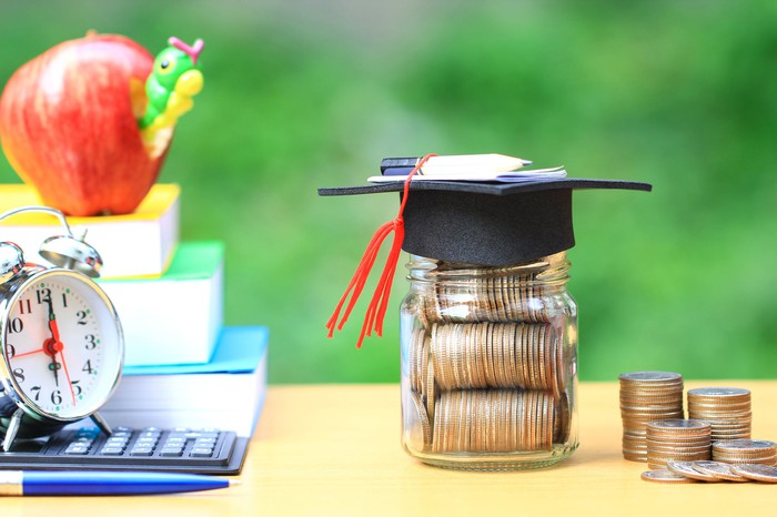 A graduation hat on a glass jar filled with coins and books beside it.