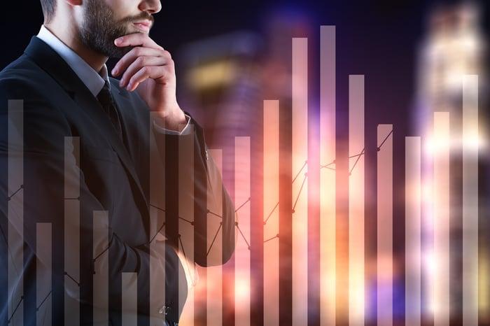 Man looking at rising stock chart.