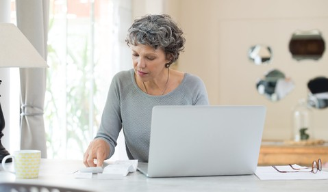 mature senior woman sitting at table in front of computer looking at receipts paying bills documents finance