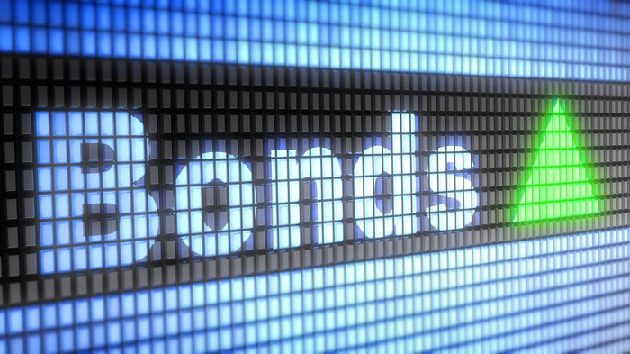 The word bonds in blue electronic block letters next to a green arrow pointing upward