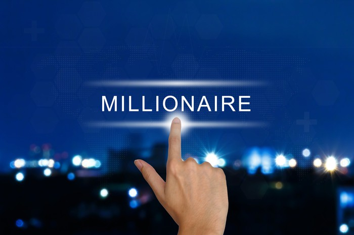 A finger is pointing to the word millionaire, against a backdrop of a city at night, all lit up.