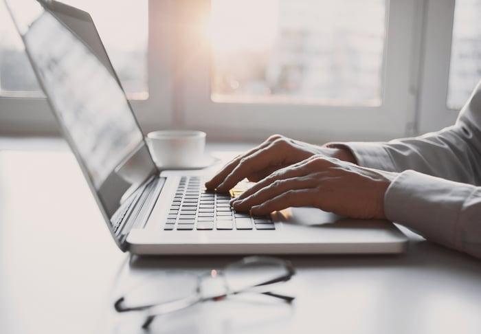 Man typing on a laptop.