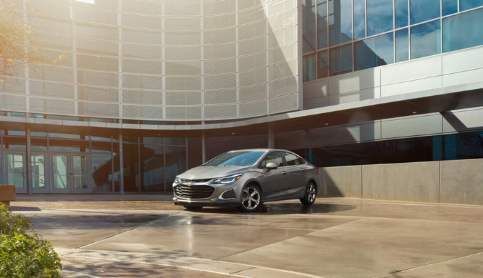 A gray Chevy Cruze parked in front of a building.
