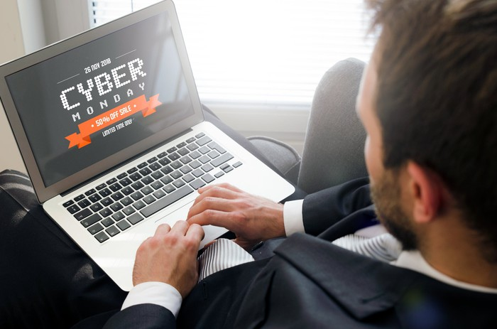 A man sits at a laptop with an illustration that says Cyber Monday.