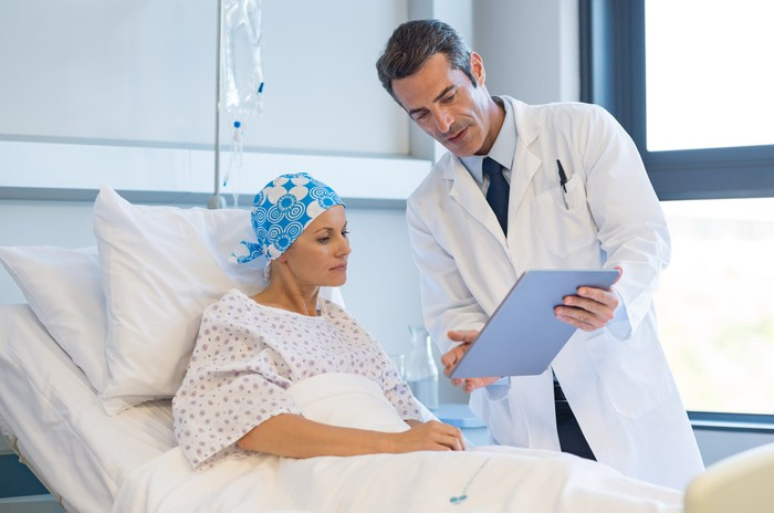 A patient in a hospital bed with a blue bandanna on her head looks at a chart a doctor is showing her.