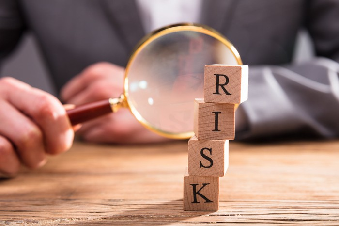 "Businessman holding magnifying glass up to stacked wooden blocks spelling ""risk"""