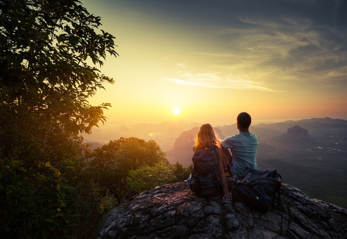 Couple sitting on mountaintop watching sunrise.