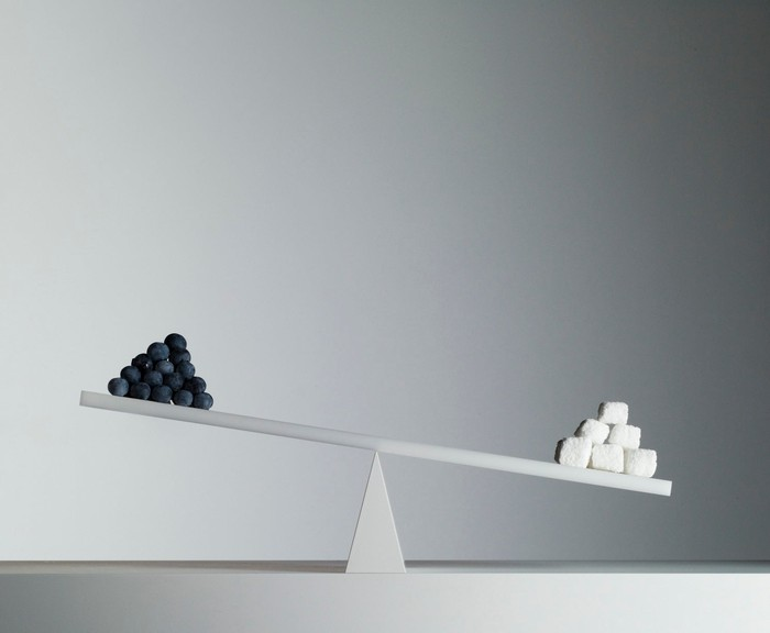 White seesaw with black balls on one size and white balls on the other, in a white room.