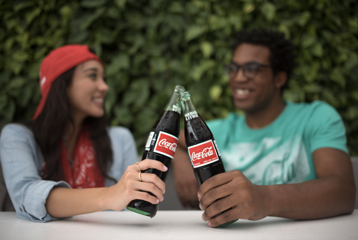 A young woman and young man giving cheers to each other while holding bottles of Coke.