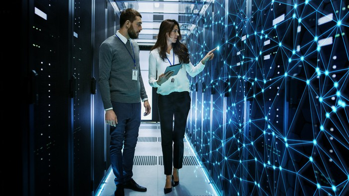 A man and woman standing in an aisle of large computer servers with a web of bright blue dots overlaying the servers the woman is point to.