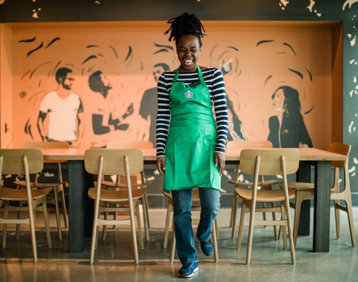 A female Starbucks employee standing in the middle of a store dining room and laughing with her eyes closed.