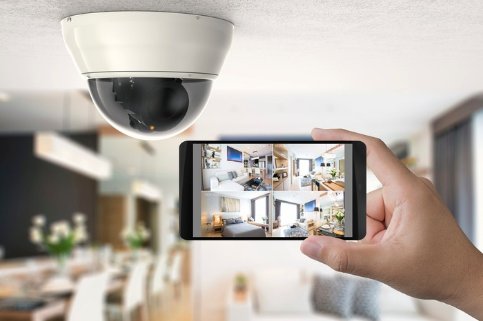 A security camera next to a mobile phone displaying images from it
