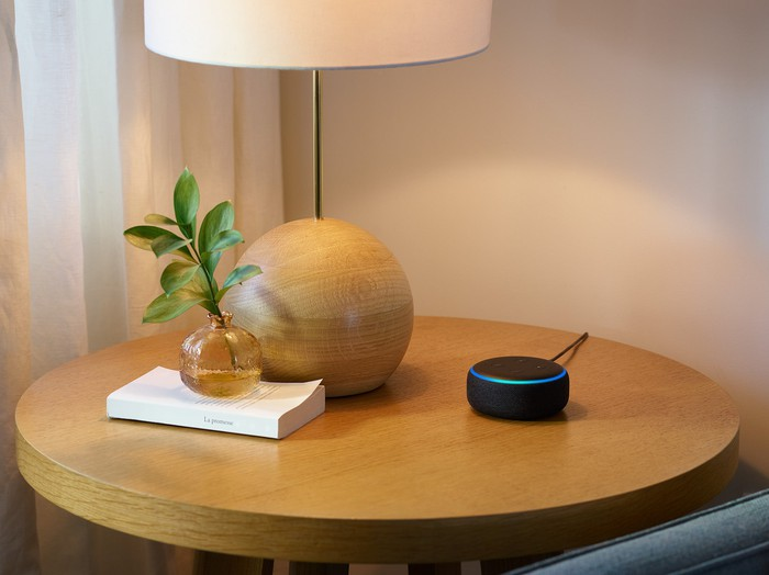 Echo Dot device on a side table, next to a lamp and a small vase.