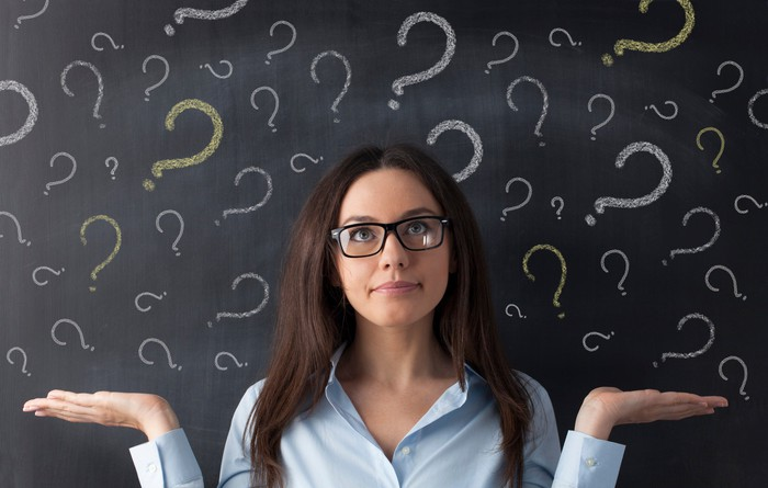 A woman shrugs in front of a blackboard covered by question marks.
