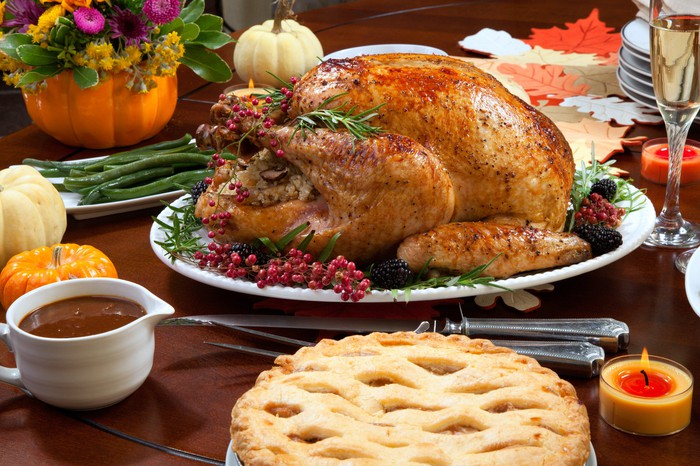 A roasted turkey surrounded by other food dishes and fall decorations.