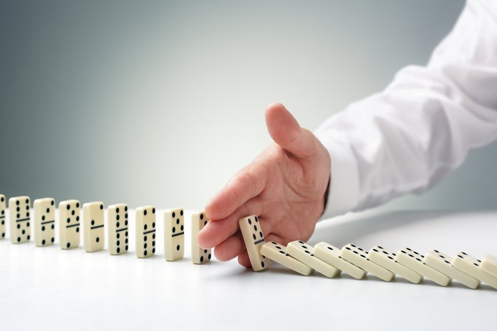 Businessman's hand stops a row of dominoes from falling, connoting a successful defensive strategy.