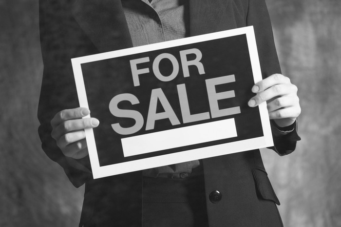 A businessman in a suit holding a for sale sign in his hands.