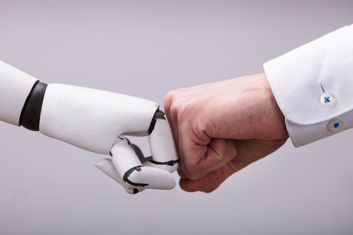 A robot and a human hand bumping fists.