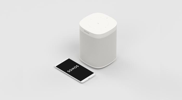 A white Sonos speaker next to a smartphone running the Sonos app.