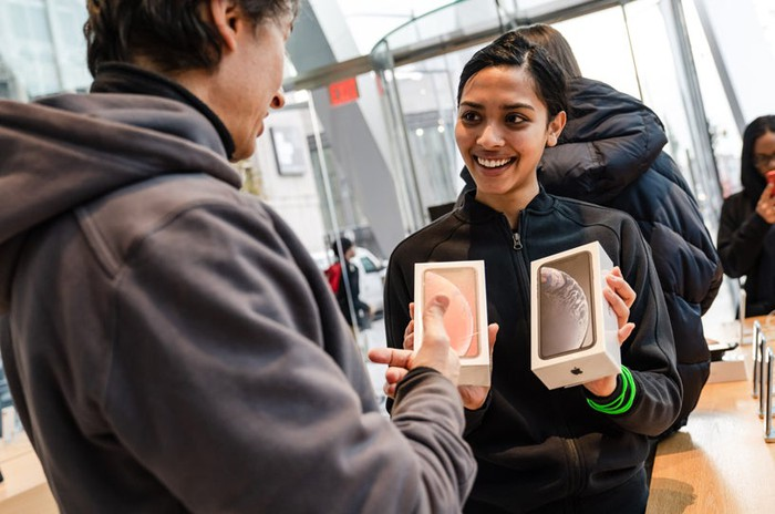 A woman in a glass atrium holding two boxed iPhones, smiling at an individual facing her