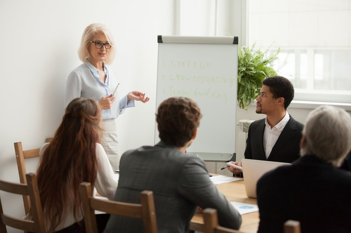 Professionally dressed woman standing and addressing a group of professionals