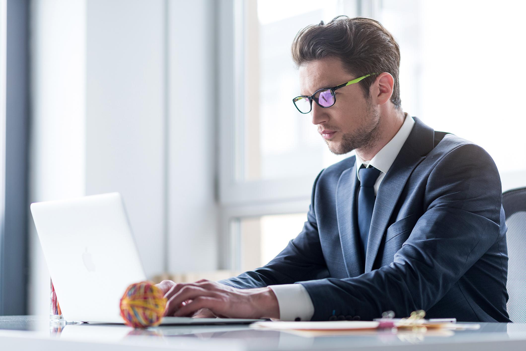 Man in suit typing on laptop.