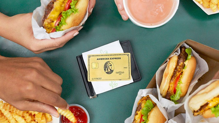 American Express gold card sitting on top of a wallet in the middle of a table with cheeseburgers and fries encircled around it.