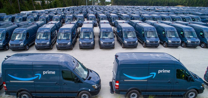 Parking lot full of blue vans with the Amazon Prime upward-sloping arrow logo on them.