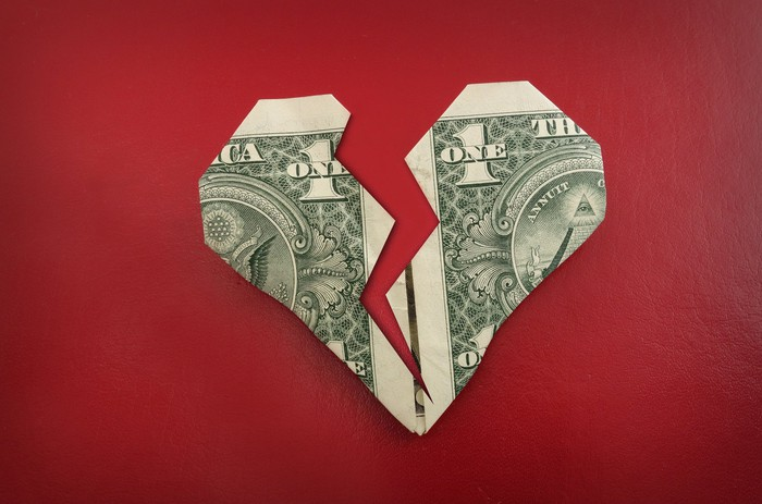 A dollar bill that has been folded into a heart is shown, against a red background -- it's also shown as breaking in two.