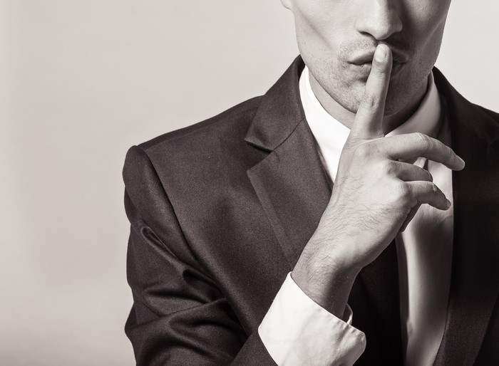Part of a man in a suit is shown -- we see him holding a finger against his lips, signifying a secret.