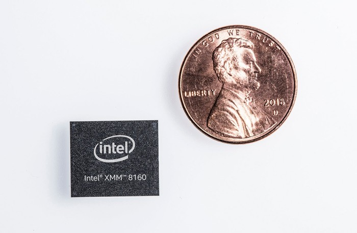 An Intel XMM 8160 chip next to a penny in a size comparison, with the chip being smaller.