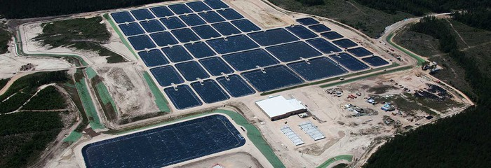 Aerial view of a fish hatchery with rectangular pools lined by Raven Industries' engineered films.