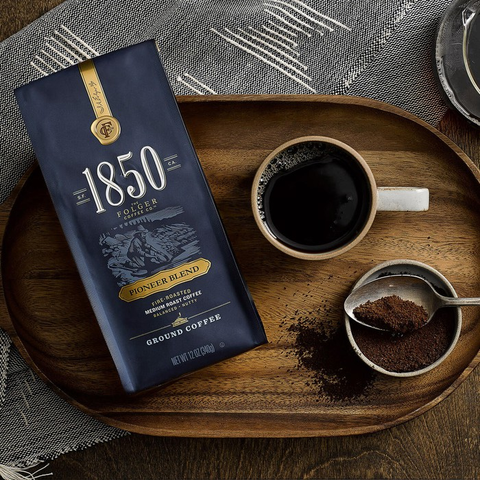 "Package of premium ""1850"" ground coffee on wooden serving tray with coffee cup."