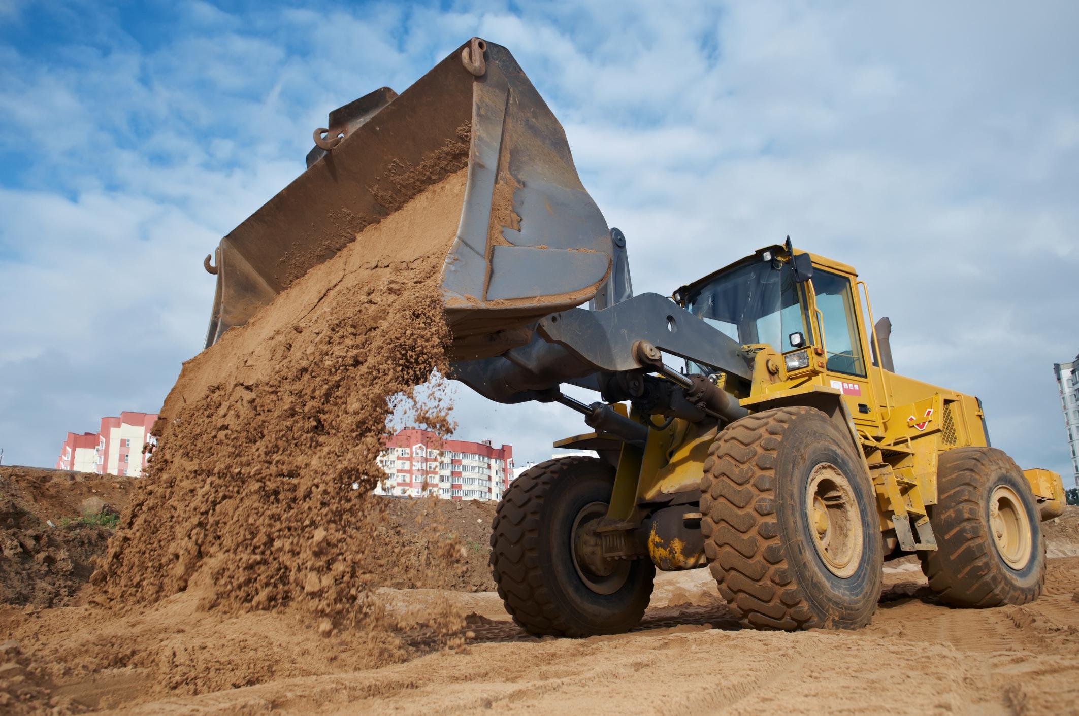 Excavator dumping sand.