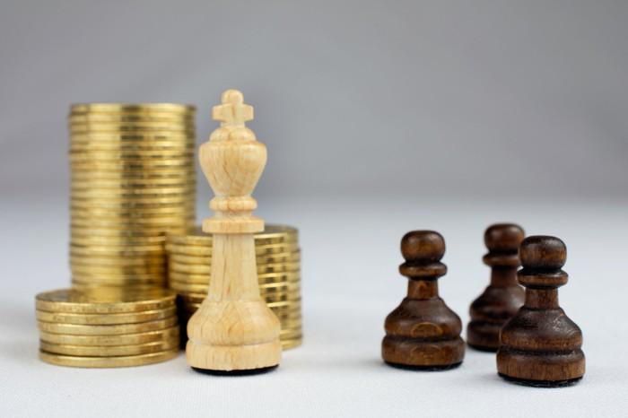 Chess pieces in front of stacked gold coins