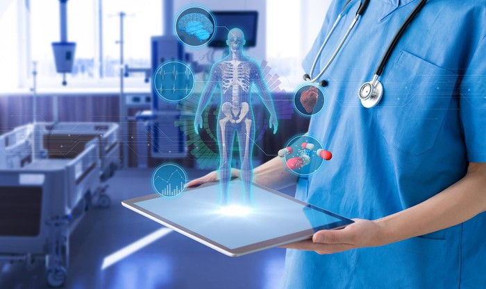 Doctor holding tablet in hospital room with medical technology icons above the tablet.