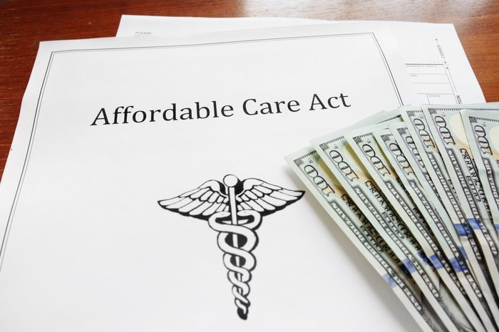 """Papers labeled """"Affordable Care Act"""" on a desk, with a fan of $100 bills."""