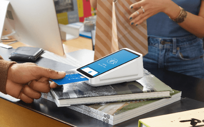 A hand swiping a credit card through Square's digital checkout terminal.