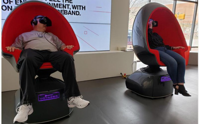 "Two people sitting in egg-shaped chairs at Verizon 5G Experience Labs, watching the ""First Man"" moon landing recreation."