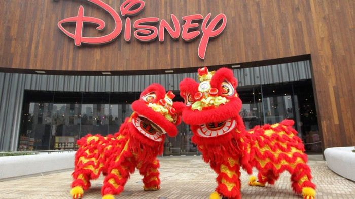 Two Chinese dragons in front of a Disney sign at a park.