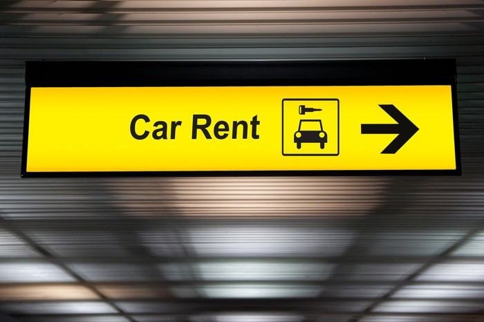 Yellow car rental sign at an airport.