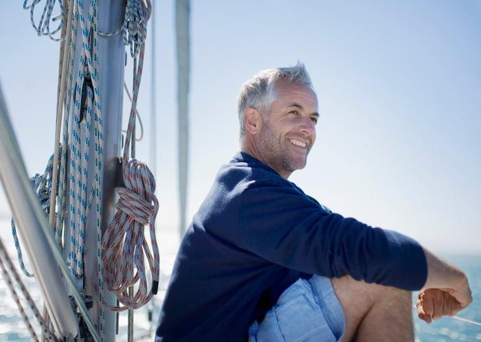 Older man on a boat, smiling.